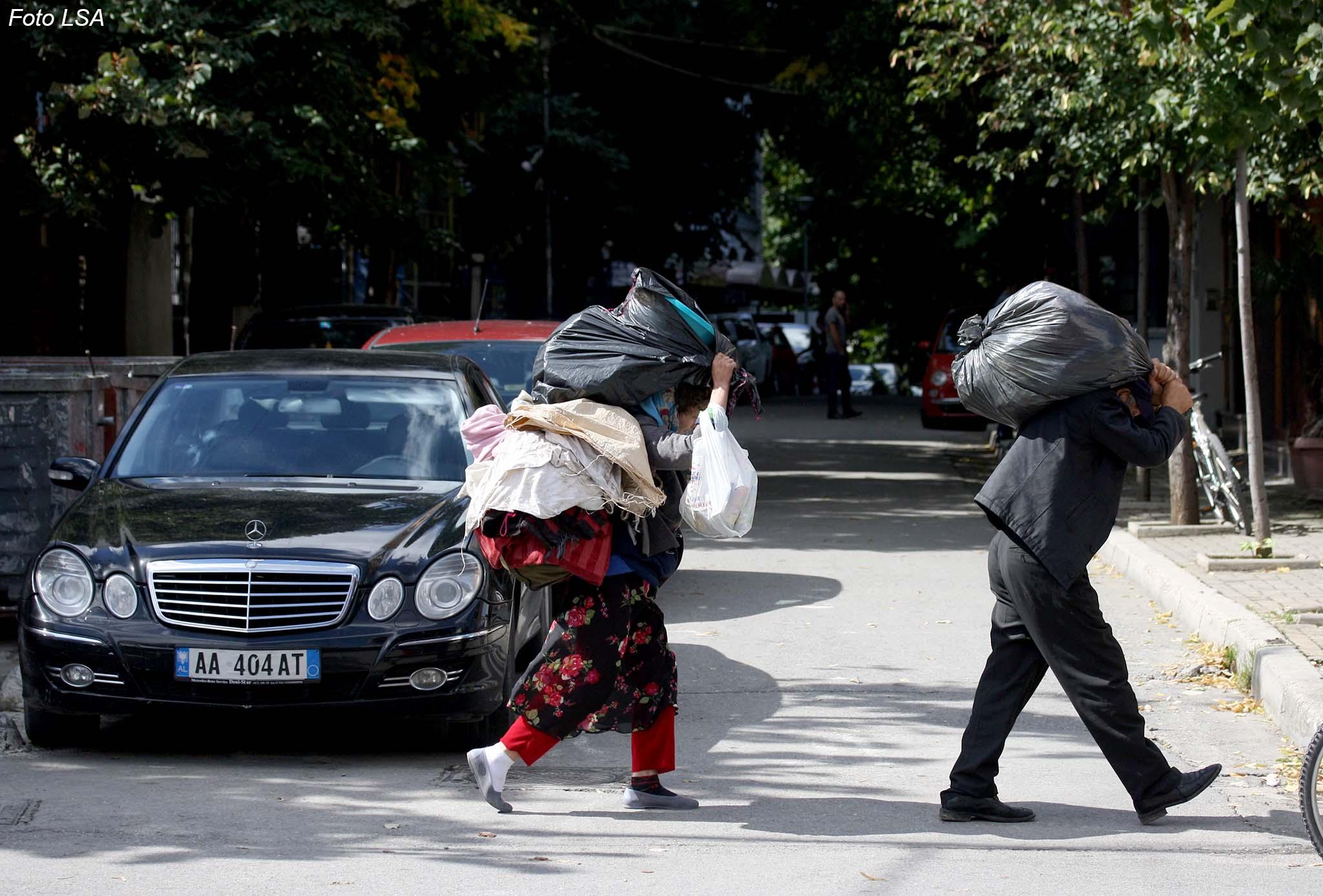 Nje cift te moshuarish, duke mbajtur ne krahe qese plastike te mbushura me rroba, prane rruges se Elbasanit./r/n/r/nA couple of elderly, by carrying the plastic bag filled with clothes, near Elbasan road.