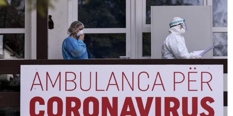 "Members of the University Clinical Center of Kosovo in protective gear walk past a sign reading ""Ambulance For Coronavirus"" at the University Clinical Center of Kosovo in Pristina on March 14, 2020. - Kosovo reported its first coronavirus (COVID-19) case on March 13, 2020, in a 22-year-old Italian woman and a 77-year-old Kosovar man, both recently returned from Italy. (Photo by Armend NIMANI / AFP)"