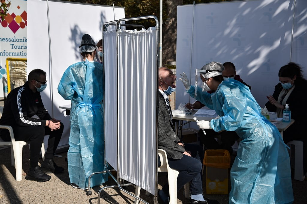 "People are tested for Covid-19 by medical staff in the waterfront of Thessaloniki on October 29, 2020 as Greek Prime minister said he will announce a new ""action plan"" on Ocotber 30 to help control the recent jump in infections, while adding that the regionals of Thessaloniki, Larissa and Rodopi, northern and central Greece, will go into lockdown following localized spikes in coronavirus cases. (Photo by Sakis MITROLIDIS / AFP)"