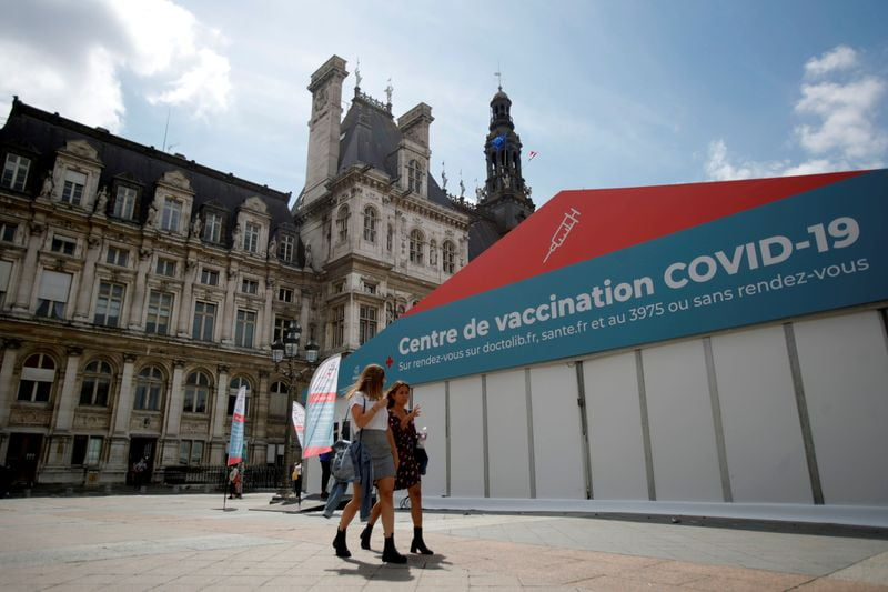 FILE PHOTO: Women walk past a coronavirus disease (COVID-19) vaccination center installated in front of Paris town hall, France, July 7, 2021. REUTERS/Sarah Meyssonnier